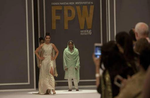 Pakistan's gang rape victim Mukhtar Mai walks on to stage during a fashion show in Karachi, Pakistan