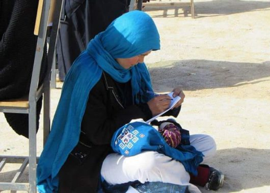 Photo Afghan Woman Nursing Baby Exam