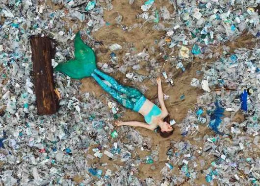 mermaid-protest:-activist-dressed-as-mermaid-lies-on-beach-filled-with-plastic
